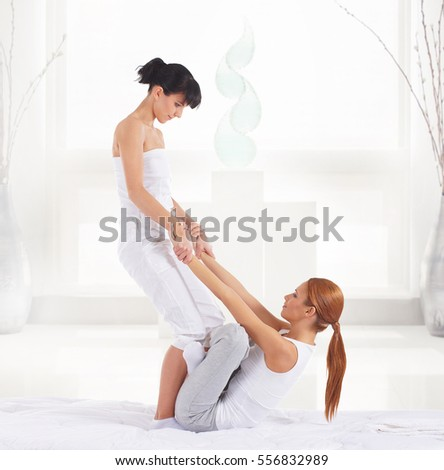 Young woman getting traditional Thai stretching massage by therapist over spa salon background