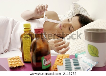 young woman, girl lying in bed and checking temperature, some drugs on a table in the foreground
