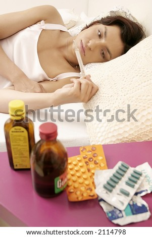 young woman, girl lying in bed and checking temperature, some drugs on a table in the foreground - stock photo