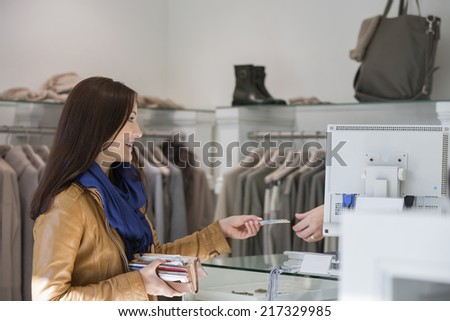 Young woman giving credit card to cashier - stock photo