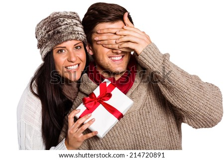 Young woman giving gift to boyfriend on white background