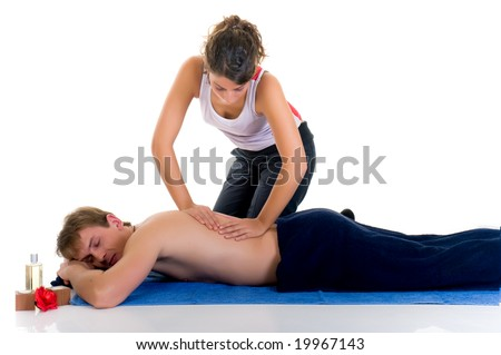 Young woman giving massage to handsome young man in spa center. Studio, white background. - stock photo