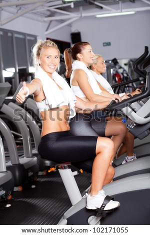 young woman giving thumb up on gym bike - stock photo