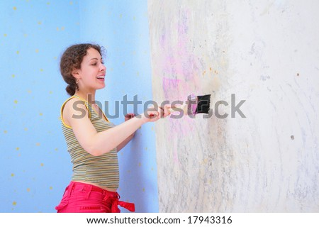 young woman glues wall-paper