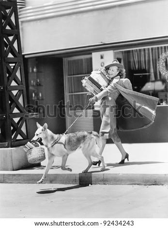 Young woman going shopping with her German shepherd and carrying presents - stock photo