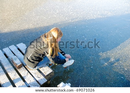 Young woman going to skate on frozen lake putting her ice skating shoes on. - stock photo