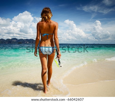Young woman going to snorkel in clear sea - stock photo