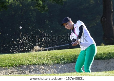 Young woman golfer chipping golf ball out. - stock photo