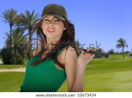young woman golfing on the course - stock photo