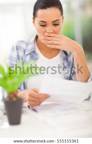 young woman got shocked when receive her monthly bank statement - stock photo