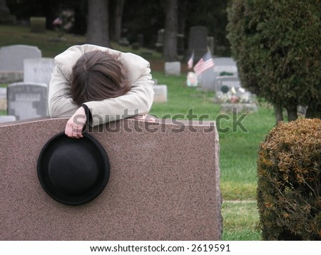 Young woman grieving at graveside. - stock photo