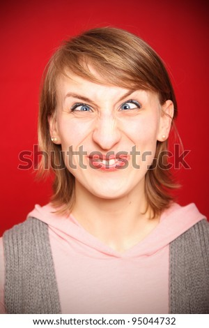 young woman grimacing with crossed eyes in front of red background - stock photo