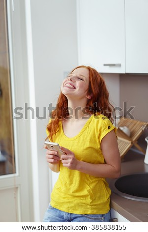 Young woman grinning with joy and happiness as she stands in her kitchen clutching her mobile phone and looking up into the air - stock photo