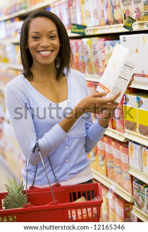 Young woman grocery shopping in supermarket - stock photo