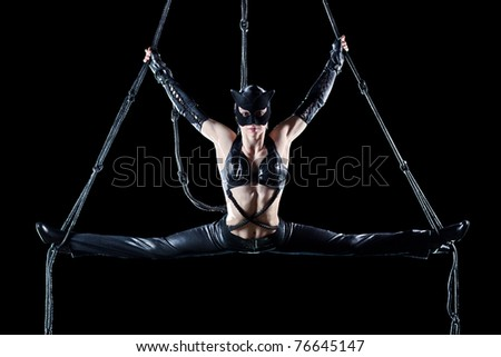Young woman gymnast in cat suit. On black background. - stock photo