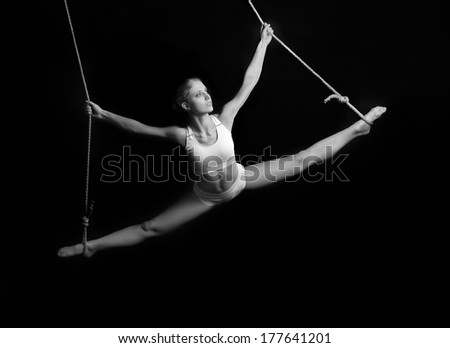 Young woman gymnast. On black background - stock photo