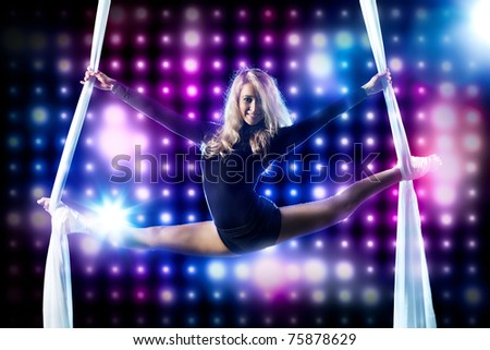 Young woman gymnast. On black background with lights. - stock photo