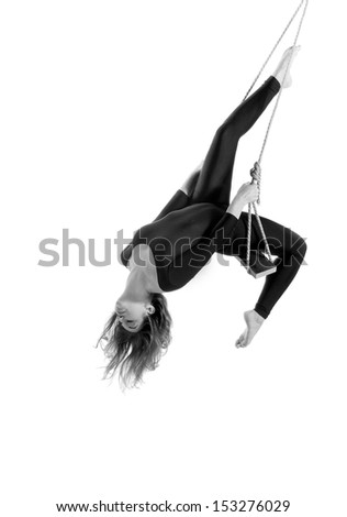 Young woman gymnast on rope on white  background, black and white