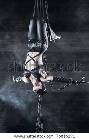 Young woman gymnast. On wall background with smoke effect.