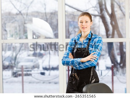 Young woman hairdresser in apron standing near window - stock photo