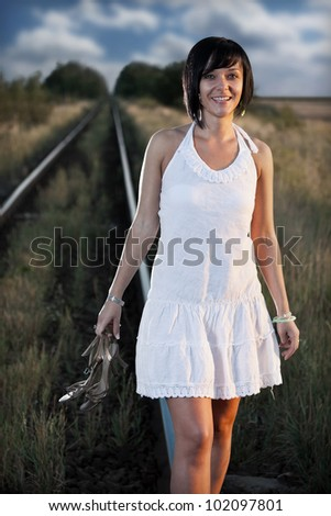 Young woman hand with shoes on the railway - stock photo