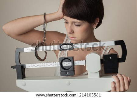 Young woman handcuffed to a medical weight scale. - stock photo