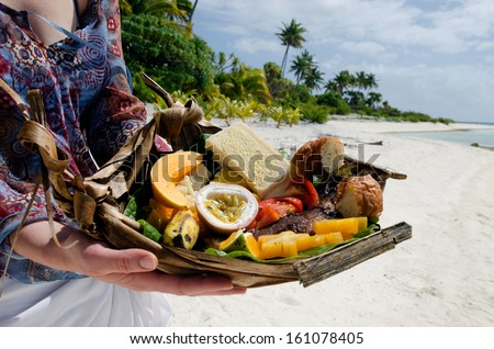 Young woman hands carry tropical food of grilled fish, fruits and vegetables dish served on deserted tropical island in Aitutaki lagoon, Cook Islands. - stock photo