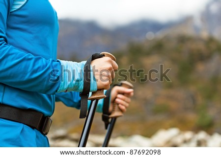 Young woman hands nordic walking in mountains