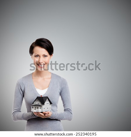 Young woman hands small toy house in front of herself, isolated on grey - stock photo