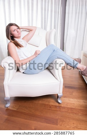 young woman hanging around in armchair