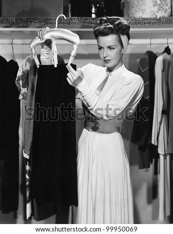 Young woman hanging up a skirt in the closet - stock photo