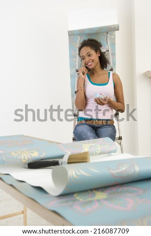 Young woman hanging wallpaper, resting on ladder with mug, using mobile phone, smiling - stock photo
