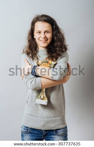 Young woman happily embraces cup victory. On a gray background. - stock photo
