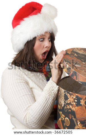 Young woman happily shocked when she opens a Christmas present; isolated on a white background. - stock photo