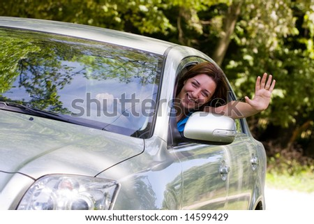 Young woman happy about her new car - stock photo