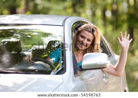 Young woman happy about her new car