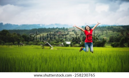 young woman happy jumping on cornfield in raining season, pretty girl relaxing outdoor - stock photo