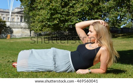 Young woman happy laying on the grass
