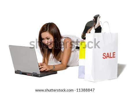 young woman happy shopping online on a laptop with shopping by her side with angel wings - stock photo