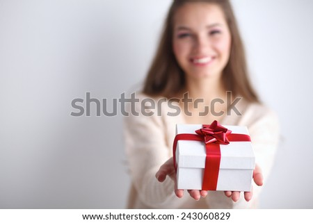 Young woman happy smile hold gift box in hands, isolated over grey - stock photo