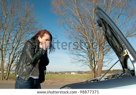 young woman has a car breakdown - stock photo