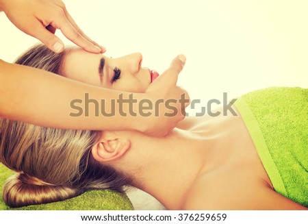 Young woman has face massage. - stock photo
