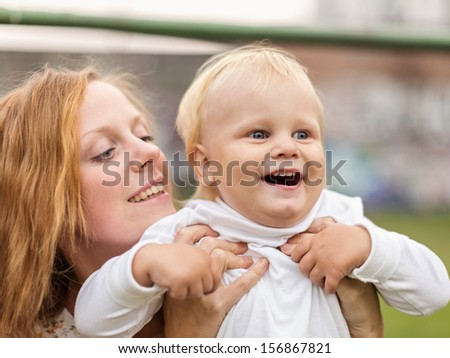 Young Woman Has Lifted the Little Boy, and He Delightfully Looks Afar