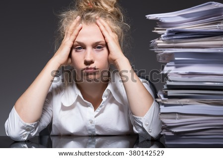 Young woman has lots of paperwork in the office  - stock photo
