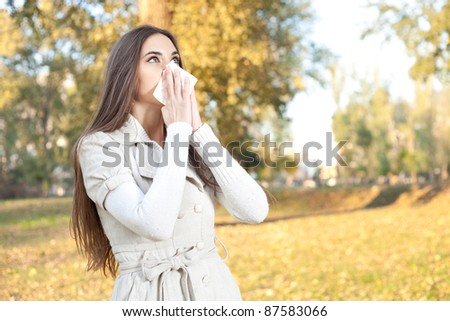 young woman have flu, autumn park - stock photo