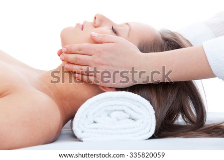 Young woman having a classical massage lying on white bed