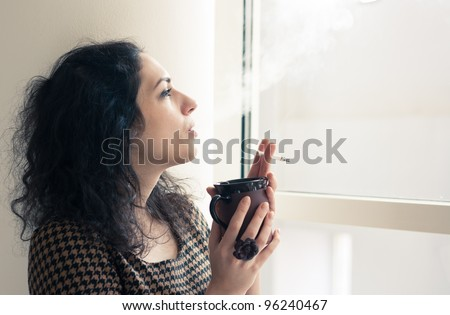 Young woman having a coffee and cigarette break indoors in a smoking room - stock photo