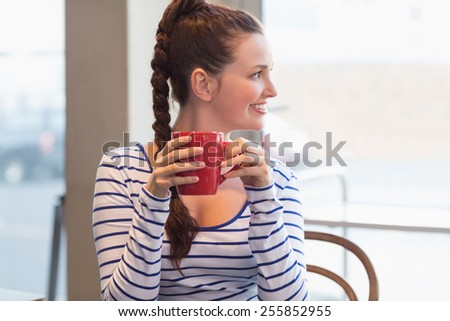 Young woman having a coffee at the cafe - stock photo