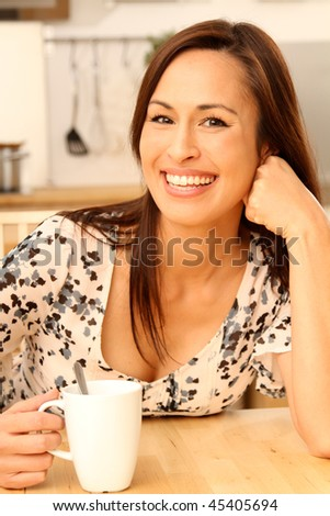 young woman having a cup of coffee in the morning in her kitchen