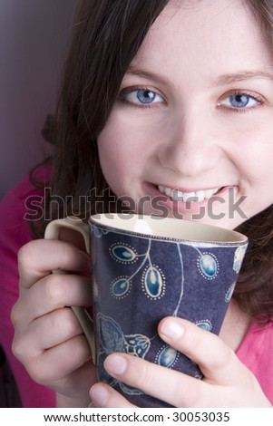 Young woman having a cuppa, shot vertical. - stock photo